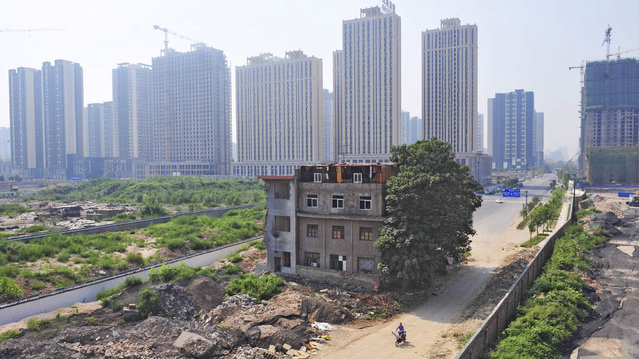 A man rides his bicycle past a partially demolished building in the middle of a street next to residential construction sites in Xi'an, August 14, 2013. A family of 7 still lived in the three-storey building without electricity and water after a demolition project in the region took place in 2010. According to local media, the owner of the house refused to move as a protest against a land dispute lawsuit between him and his brother, which he lost. (Photo by Reuters/Stringer)