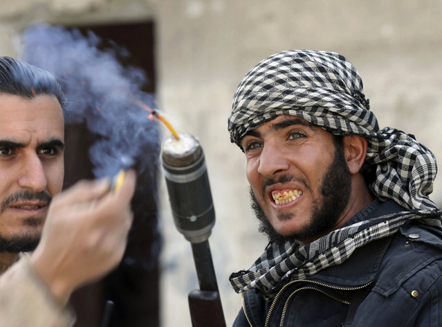"""Fighters from the """"Free Syrian Army's"""" Tahrir al Sham brigade use a shotgun to fire an improvised grenade at Syrian Army soldiers in the Arabeen neigbourhood of Damascus February 9, 2013. (Photo by Goran Tomasevic/Reuters)"""