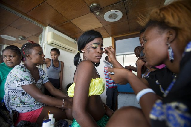 A makeup artist applies eye shadow to a dancer's eyelid during preparations for Carnival celebrations at the national stadium, in Port-au-Prince, Haiti, Monday, February 16, 2015. (Photo by Dieu Nalio Chery/AP Photo)