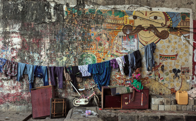 A homeless Indian girl sits on a toppled piece of furniture as she has a meal in front of a mural in a downtown street of Mumbai, India, 07 January 2016. According to a recent report in an Indian national newspaper more than 9,000 children in Mumbai go hungry every day and the first-ever census of street children conducted by the Tata Institute of Social Sciences (TISS) and the voluntary organization Action Aid India suggest that more than 37,000 children live on the streets of the Indian metropole. (Photo by Divyakant Solanki/EPA)