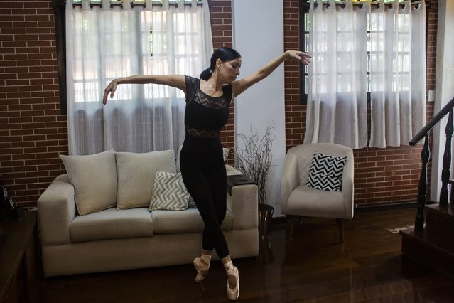 Municipal Theater ballet star Claudia Mota trains at home during the COVID-19 pandemic in Rio de Janeiro, Brazil, Friday, March 26, 2021. Mota says her floor is unfit for pointe technique and uses her banister for a barre warm-up and stretching, limiting the abilities of her body. (Photo by Bruna Prado/AP Photo)