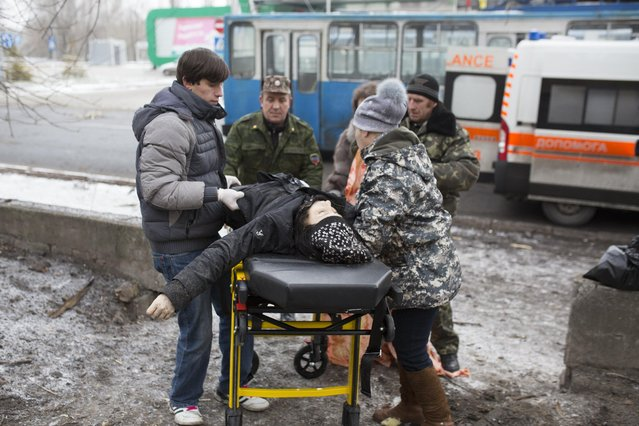 Forensic experts place a body of a victim on a stretcher after a bus station was hit during a recent shelling between pro-Russian rebels and the Ukrainian government forces in Donetsk, Ukraine, Wednesday, February 11, 2015. (Photo by Vadim Braydov/AP Photo)