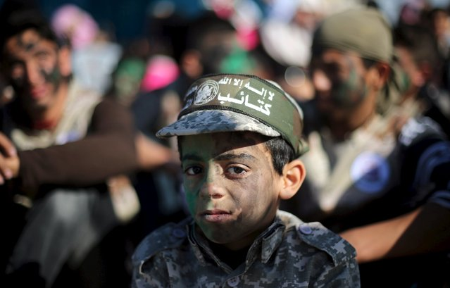 A Palestinian boy wearing the headband of Hamas' armed wing has his face painted as he watches a graduation ceremony for members of Palestinian security forces loyal to Hamas, in Gaza City January 10, 2016. (Photo by Ibraheem Abu Mustafa/Reuters)