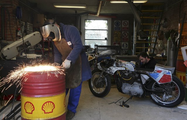 Vibrazioni's art design owner Alberto (L) cuts an oil barrel as Riccardo works on a Harley Davidson motorbike personalised with parts of an oil barrel, in Massa Lombarda central Italy, February 11, 2015. (Photo by Stefano Rellandini/Reuters)