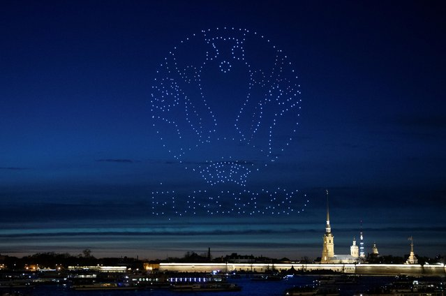 Drones forming a logo of the UEFA Euro Cup 2020 light up the sky over the Cathedral of Saints Peter and Paul in Saint Petersburg, Russia on May 2, 2021. (Photo by Anton Vaganov/Reuters)