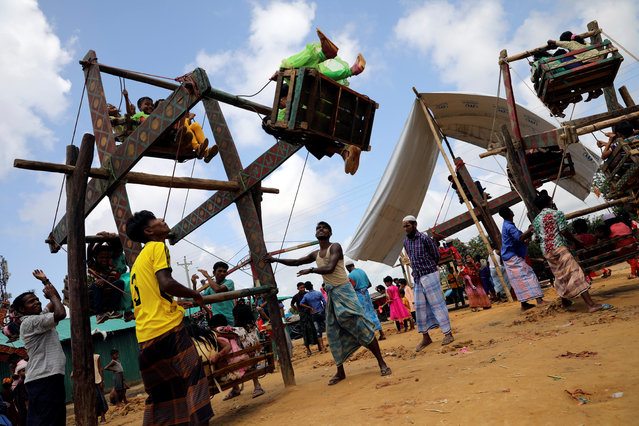 Rohingya refugee children ride on human powered ferris wheels on the day of Eid al-Adha in the Kutupalong refugee camp in Cox's Bazar, Bangladesh, August 22, 2018. (Photo by Mohammad Ponir Hossain/Reuters)