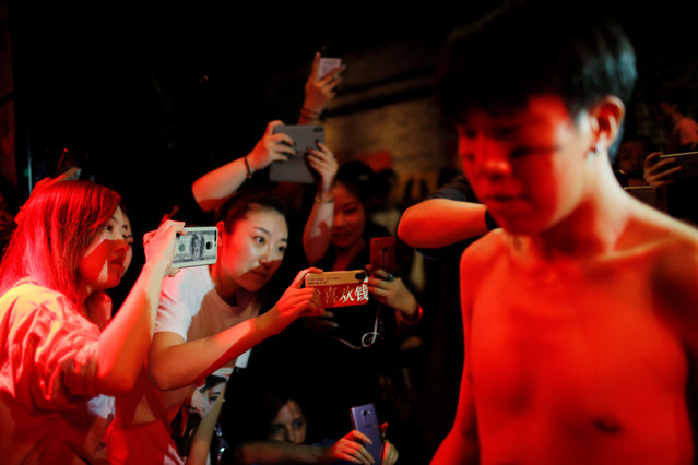 Spectators watch as Viktor Liu waits to be suspended from hooks pierced through his skin by professional body artist Wei Yilaien at a bar in Shanghai, China on September 16, 2018. (Photo by Aly Song/Reuters)
