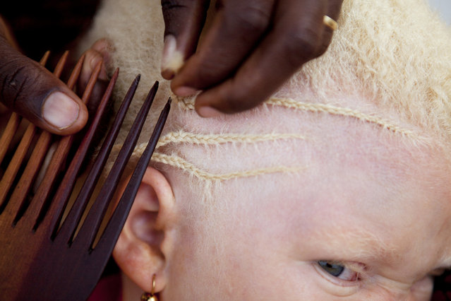 In this August 27, 2012 photo, Janet Jotham braids the hair of her daughter Lucia Jotham, 8, during a visit to see her two children living at the Kabanga Protectorate Center in Kabanga, Tanzania. (Photo by Jacquelyn Martin/AP Photo)