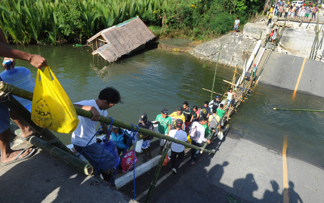 Villagers of Maribojoc, Bohol island, central Philippine use bamboo ladders to cross a bridge on October 18, 2013, that was toppled by the 7.1 magnitude quake that hit the area on October 15, leaving over 170 dead.  Days after the quake, transport and travel remained a major challenge in the island of 1.2 million with people forced to journey for hours just to get simple necessities. (Photo by Jay Directo/AFP Photo)
