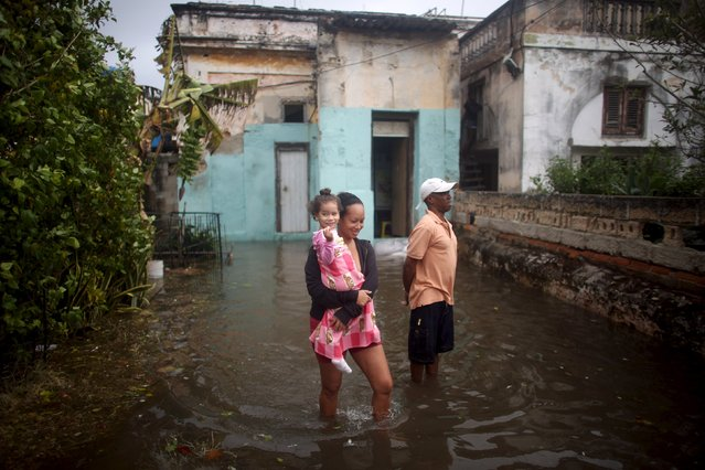 A family checks a flooded street in front of their home in Havana, January 23, 2016. (Photo by Alexandre Meneghini/Reuters)