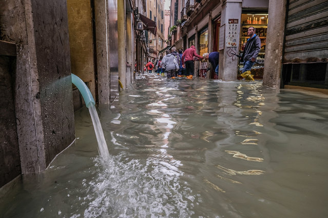 "Water is drained from a store by an electric pump on October 29, 2018 in Venice, Italy. Due to the exceptional level of the ""acqua alta"" or ""High Tide"" that reached 156 cm today, Venetian schools and hospitals were closed by the authorities, and citizens were advised against leaving their homes. (Photo by Stefano Mazzola/Awakening/Getty Images)"