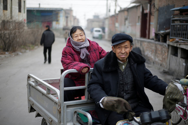 74-year-old villager Wu Chongqing and his wife Zha Shuzhen, 72, drive to a Catholic church for a Christmas eve mass on the outskirts of Taiyuan, North China's Shanxi province, December 24, 2016. (Photo by Jason Lee/Reuters)
