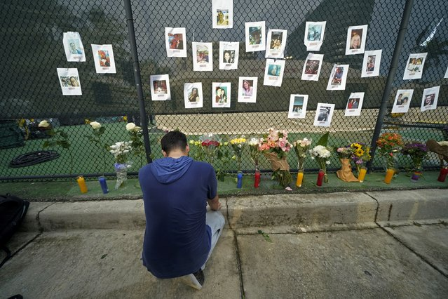 Leo Soto, who created this memorial with grocery stores donating flowers and candles, pauses in front of photos of some of the missing people that he put on a fence, near the site of an oceanfront condo building that partially collapsed in Surfside, Fla., Friday, June 25, 2021. (Photo by Gerald Herbert/AP Photo)