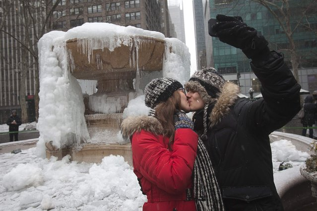 "Maria Trukhan (L) and Michael Gridin from Brooklyn take a ""selfie"" photo as they kiss in front of the frozen fountain in Bryant Park on Valentine's Day in the Manhattan borough of New York February 14, 2015. (Photo by Carlo Allegri/Reuters)"