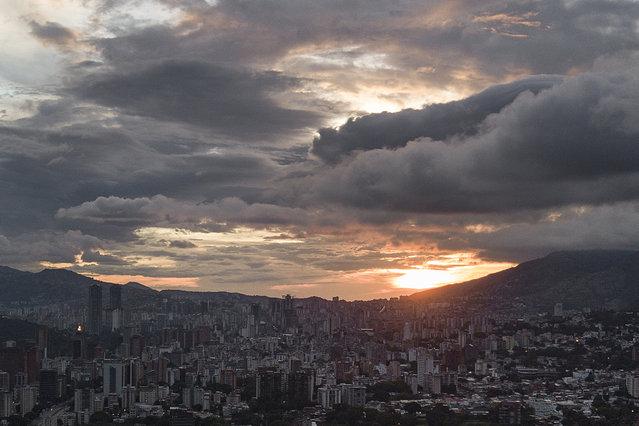 The sun sets over Caracas, Venezuela, Tuesday, May 18, 2021, amid the coronavirus pandemic. (Photo by Matias Delacroix/AP Photo)