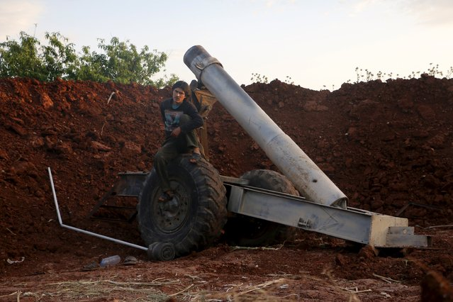 A Tajammu Al-Ezza brigade fighter rests beside a locally made weapon before using it to fire towards forces loyal to Syria's President Bashar Al-Assad stationed at Al-Zlakiet checkpoint, in the Hama countryside May 9, 2015. (Photo by Mohamad Bayoush/Reuters)
