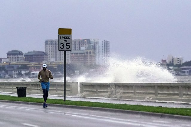 A jogger makes his way along Bayshore Blvd., in Tampa, Fla. as a wave breaks over a seawall, during the aftermath of Tropical Storm Elsa Wednesday, July 7, 2021. (Photo by John Raoux/AP Photo)