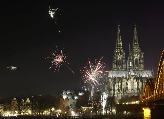 Fireworks explode near to the High Cathedral of Saint Peter during New Year celebrations for 2017 in Cologne, Germany, January 1, 2017. (Photo by Wolfgang Rattay/Reuters)