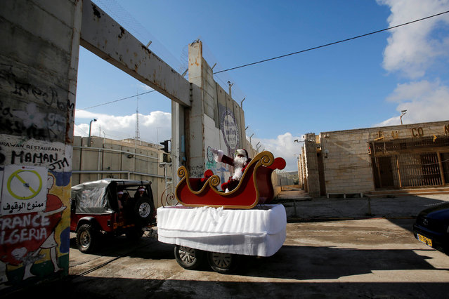 A man dressed as Santa Claus gestures as the convoy of the acting Latin Patriarch of Jerusalem Pierbattista Pizzaballa arrives through an Israeli checkpoint to attend Christmas celebrations in Bethlehem, in the Israeli-occupied West Bank on December 24, 2018. (Photo by Mussa Qawasma/Reuters)