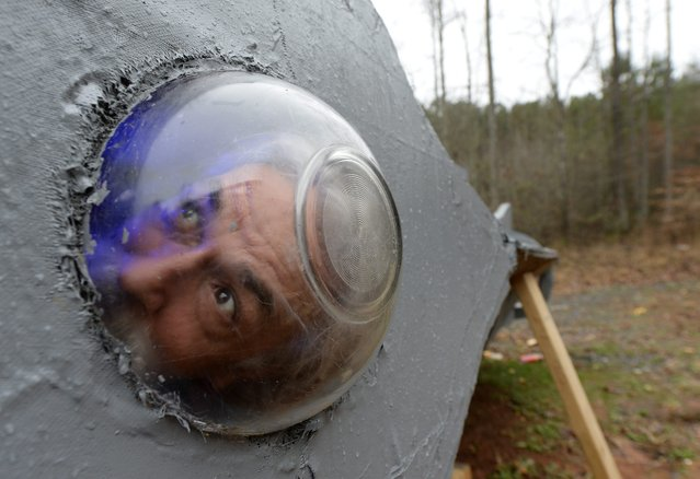 "Danny McWilliams, 56, looks out a bowl porthole on his replica of Walt Disney movie version of the Nautilus submarine from Jules Verne's ""20,000 Leagues Under the Sea"" at his rural home in Ellijay, Georgia, USA, 04 December 2013. (Photo by Erik S. Lesser/EPA)"