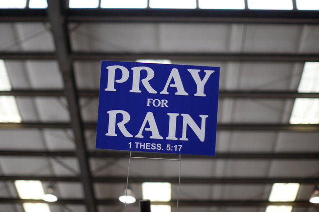 A sign advising to pray for rain hangs above an exhibit area at the 47th Annual World Ag Expo in Tulare, February 12, 2014. (Photo by David McNew/Reuters)