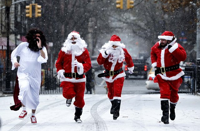 Revelers dressed as Santa Claus run as they arrive at Tompkins Square Park to take part in the annual SantaCon bar crawl in New York City. (Photo by Kena Betancur/Getty Images)