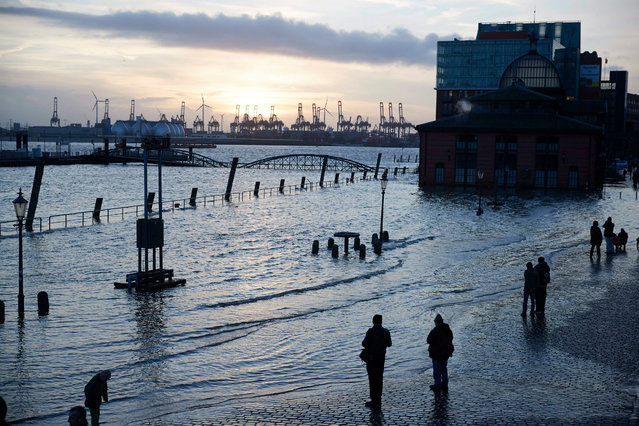"""People gather to look at water flooding the area around the landmark """"Altonaer Fischmarkt"""" (Fish Auction Hall) in Hamburg, Germany, 12 January 2017. Low """"Dieter"""" has swept over the north of Germany. (Photo by Carsten Koall/EPA)"""