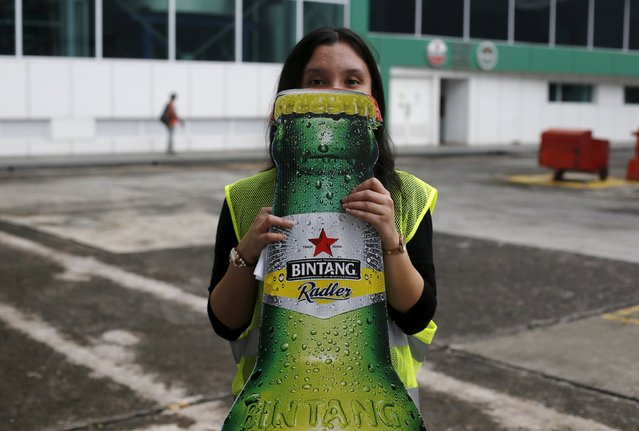 A worker of PT Multi Bintang Indonesia Tbk. holds up a cutout of a Bintang beer at a beer factory in Jakarta April 17, 2015. Two Islamic parties have proposed legislation to ban all consumption of alcoholic drinks and hand jail terms of up to two years to offenders in Indonesia, home to the world's largest Muslim population. (Photo by Reuters/Beawiharta)