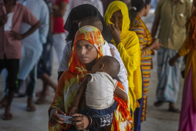Women stand in a queue to receive the vaccine for COVID-19 in Khola Bhuyan village on the outskirts of Gauhati, India, Tuesday, September 7, 2021. (Photo by Anupam Nath/AP Photo)