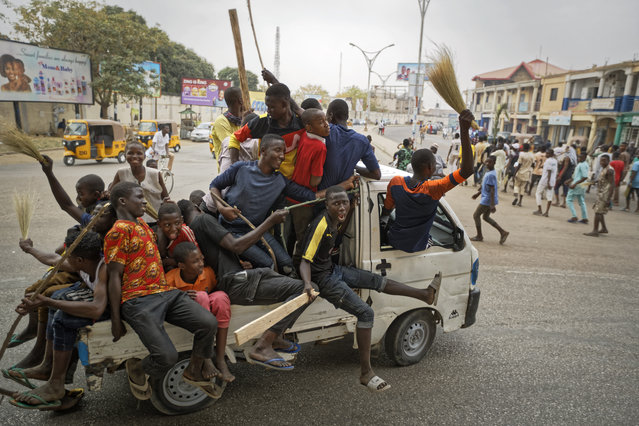 """Supporters of Nigeria's President Muhammadu Buhari, some carrying crude weapons, ride on the back of a truck as they follow a march of others to celebrate his electoral win, on a street in Kano, northern Nigeria Wednesday, February 27, 2019. Buhari on Wednesday defended his sweeping win of a second term as free and fair and appealed to a """"common love of country"""" as his top challenger vowed to go to court with allegations of fraud. (Photo by Ben Curtis/AP Photo)"""