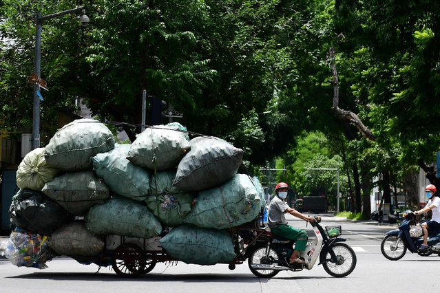 A scrap dealer carries stacks of plastic waste on his make-shift motorcycle-cart in Hanoi on August 13, 2021. (Photo by Nhac Nguyen/AFP Photo)