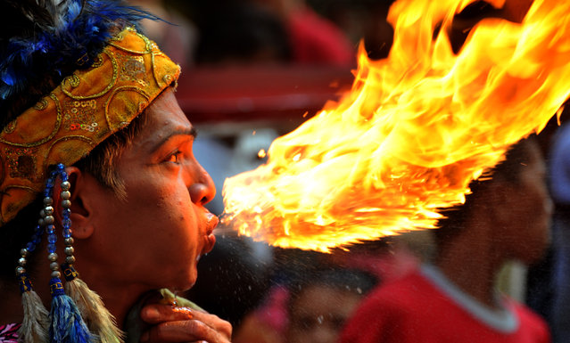 A fire breather performs in Chinatown in Manila a day before the Chinese New Year on January 22, 2012. (Photo by Noel Celis/AFP Photo)