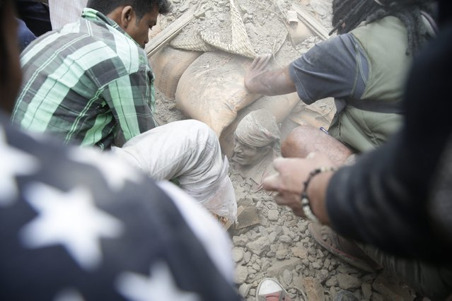 People try to free a man from the rubble of a destroyed building after an earthquake hit Nepal, in Kathmandu, Nepal, 25 April 2015. (Photo by Narendra Shrestha/EPA)