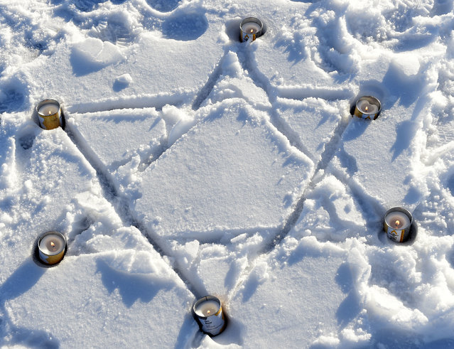 Candles burn near a Jewish star that was painted in the snow during a commemoration ceremony at the former Nazi concentration camp Buchenwald in Weimar, Germany, Friday, January 27, 2017. (Photo by Jens Meyer/AP Photo)