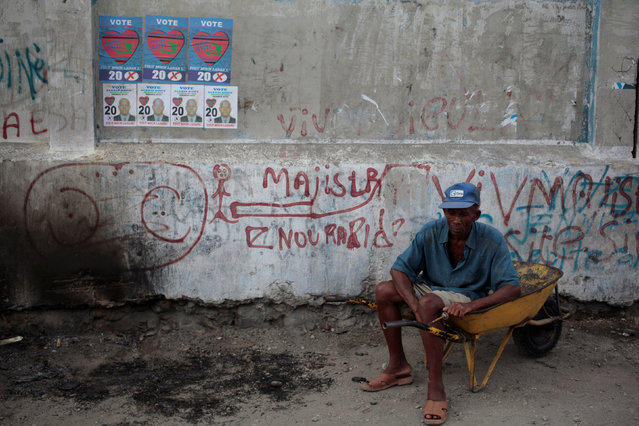 A man sits on a wheelbarrow next to electoral posters in Port-au-Prince, Haiti, January 28, 2017. (Photo by Andres Martinez Casares/Reuters)