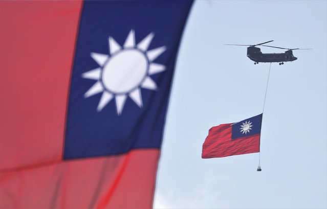 Helicopters fly over President Office with Taiwan National flag during National Day celebrations in front of the Presidential Building in Taipei, Taiwan, Sunday, October 10, 2021. (Photo by Chiang Ying-ying/AP Photo)