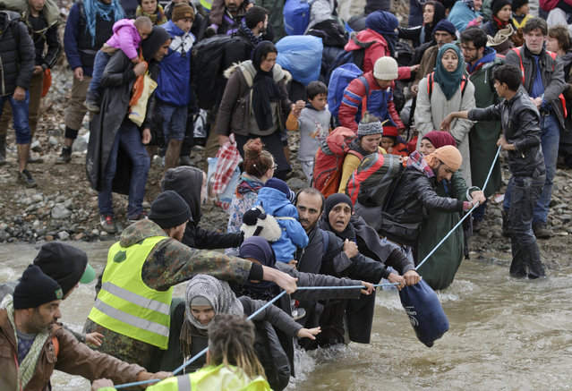Migrants cross a river, north of Idomeni, Greece, attempting to reach Macedonia on a route that would bypass the border fence, Monday, March 14, 2016. (Photo by Vadim Ghirda/AP Photo)