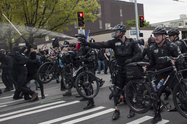 "Police use pepper spray against demonstrators during an anti-capitalist protest in Seattle, Washington, May 1, 2015. The anti-capitalist May Day march in Seattle turned violent on Friday when demonstrators threw rocks and wrenches at police, who responded by lobbing ""flashbangs"" and shooting pepper balls, according to police and media reports. International Workers' Day. (Photo by David Ryder/Reuters)"