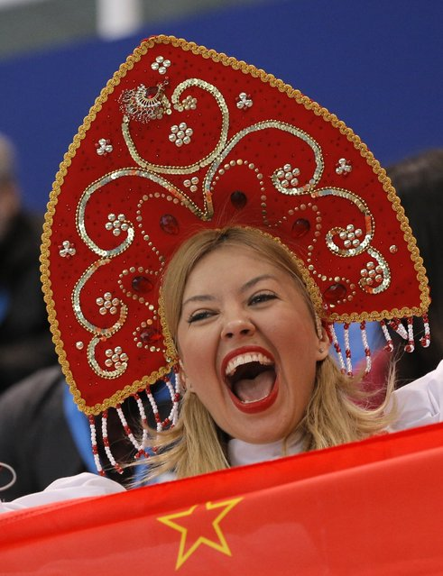 A spectator cheers as she stands behind a flag of the Soviet Union before the short track speed skating competition at the Iceberg Skating Palace during the 2014 Winter Olympics, Monday, February 10, 2014, in Sochi, Russia. (Photo by Vadim Ghirda/AP Photo)