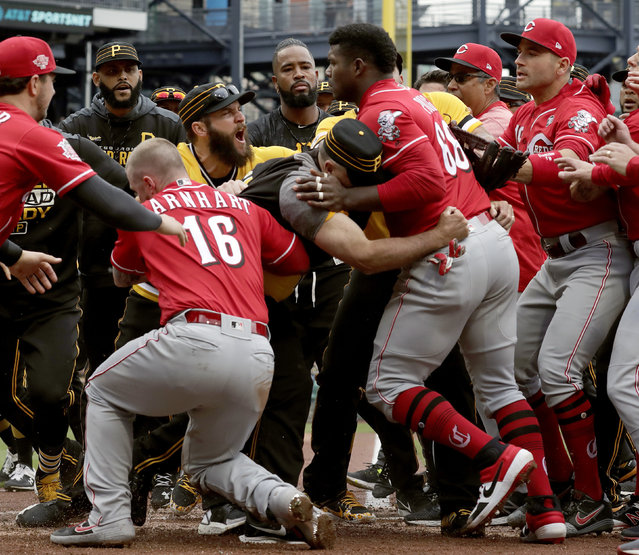 Cincinnati Reds' Yasiel Puig (66) is restrained by Pittsburgh Pirates bench coach Tom Prince, in the middle of a bench clearing brawl during the fourth inning of a baseball game in Pittsburgh, Sunday, April 7, 2019. (Photo by Gene J. Puskar/AP Photo)