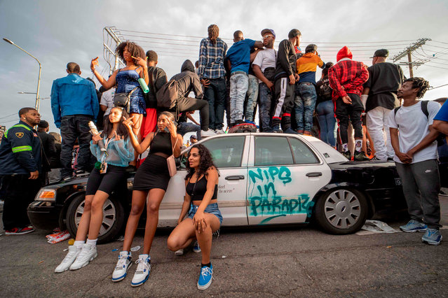 Fans and community members gather around a LAPD car along the procession route for Nipsey Hussle after his memorial at the Staples Center in Los Angeles, California, April 11, 2019. 4 people shot and 1 dead during the procession LAPD reported on late April 11, 2019 The Grammy-nominated artist was killed in front of The Marathon Clothing store he founded in 2017. (Photo by Kyle Grillot/AFP Photo)