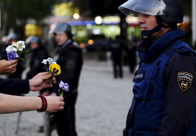 Protesters offer flowers to police in fromt of the Macedonian parliament in Skopje, Macedonia May 7, 2015. Several hundred people demanded the resignation of Prime Minister Nikola Gruevski, who stands accused by the top opposition leader of trying to cover up the death of a 22-year-old man who was beaten to death by a police officer during a post-election celebration in 2011. (Photo by Ognen Teofilovski/Reuters)