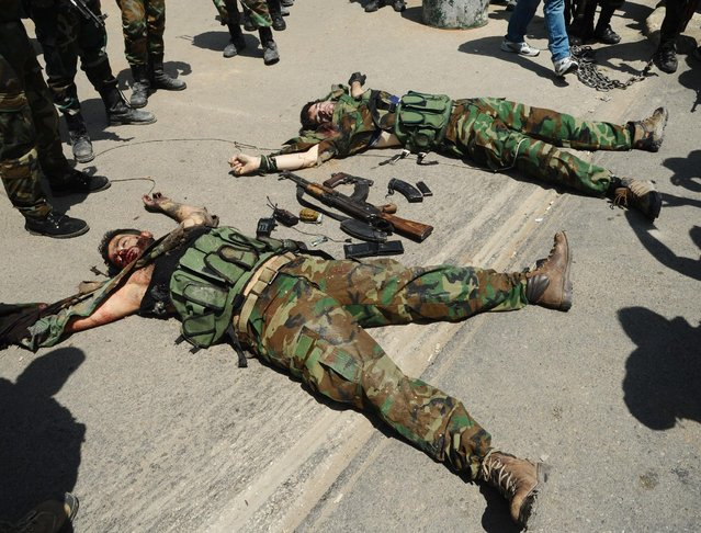 In this photo released by the Syrian official news agency SANA, bodies of fighters lie on the ground after a bombing attack in the Rokn al-Deen neighborhood, Damascus, Syria, Monday, May 4, 2015. A small group of insurgents, including a suicide bomber, carried out the attack in Damascus on Monday targeting a Syrian military logistics and supply facility, militants and activists said. (Photo by SANA via AP Photo)