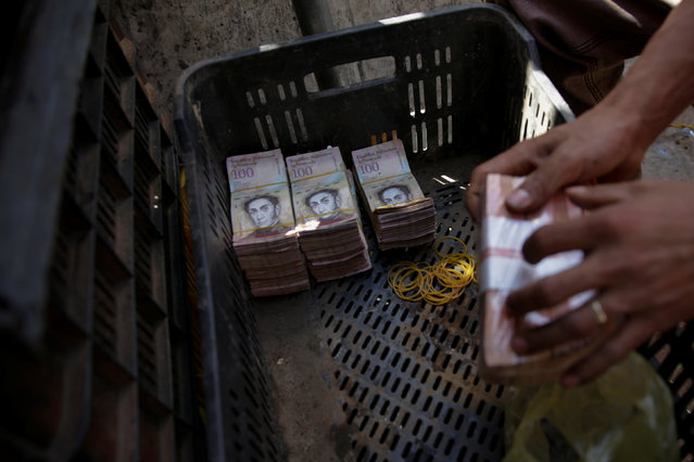 Stacks of 100 bolivar notes are seen in a plastic crate at a stall in a street market near Venezuela's Central Bank in Caracas, Venezuela December 16, 2016. (Photo by Marco Bello/Reuters)