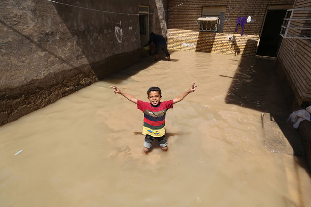 An Iranian child gestures for the camera at a flooded house in the city of Hamidiyeh, in Iran's Khuzestan province, on April 10, 2019. Authorities ordered tens of thousands of residents of the southwestern Iranian city of Ahvaz to evacuate immediately as floodwaters entered the capital of oil-rich Khuzestan province, state television reported. (Photo by Atta Kenare/AFP Photo)