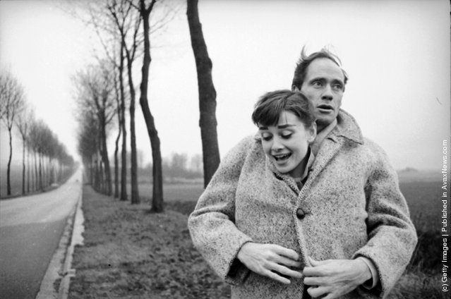 American actor Mel Ferrer buttons up his coat around his wife, actress Audrey Hepburn, on a country road outside Paris, 1956