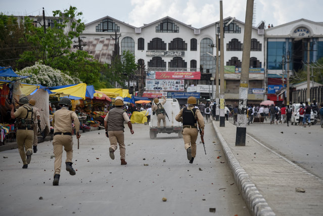 Police chase Kashmiri students after clashes during a protest following the alleged rape of a child in the region in Srinagar, India on May 15, 2019. (Photo by Idrees Abbas/Sopa Images/Rex Fetures/Shutterstock)
