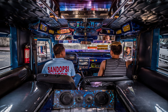33-year old chauffeur John Paul has driven a Patok jeepney for seven years. He shares the daily rides with a friend who helps by taking the fares. (Photo by Claudio Sieber/Barcroft Media)