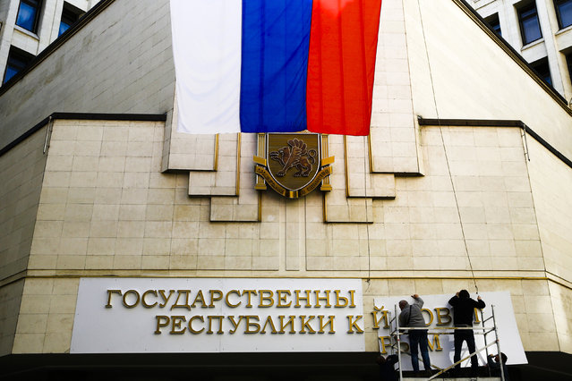 """Workers put up a new sign at the local parliament building in Simferopol March 19, 2014. Defying Ukrainian protests and Western sanctions, Russian President Vladimir Putin signed a treaty in Moscow on Tuesday making Crimea part of Russia again, but said he did not plan to seize any other regions of Ukraine. The sign reads, """"State Council of the Crimean Republic"""". (Photo by Thomas Peter/Reuters)"""