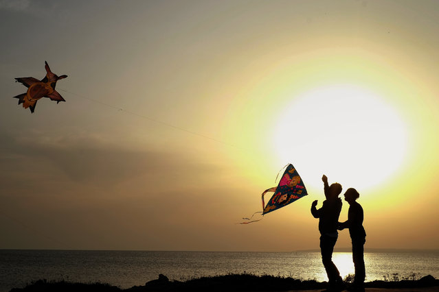 Men fly their kites during celebrations of the Orthodox Clean Monday in Ayia Napa, Cyprus, Monday, February 27, 2017. Cypriots traditionally celebrate Clean Monday, the beginning of Lent in the Eastern Orthodox Church calendar, by eating seafood to signify a break with meat-eating and the start of a 40-day fast until Easter. (Photo by Petros Karadjias/AP Photo)
